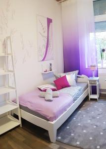 A bed or beds in a room at Center: 5min vom HBF, Düsseldorf Messe nähe.2.OG.L. Lavendel