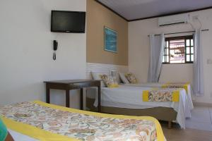 A bed or beds in a room at Pousada Daleste