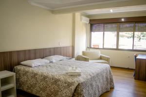 A bed or beds in a room at Hotel Letto Caxias