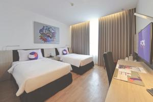 A bed or beds in a room at FOX Hotel Pekanbaru