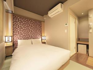 A bed or beds in a room at Asakusa Hotel Hatago