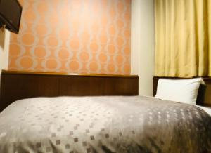 A bed or beds in a room at Urban Place Inn Kokura