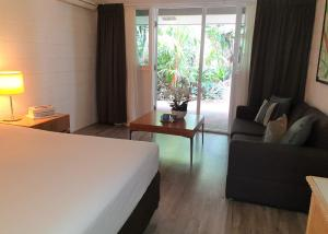 A bed or beds in a room at Rainforest Castaways Resort and Spa