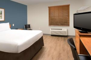 A bed or beds in a room at WoodSpring Suites Orlando Clermont - Minneola