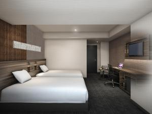 A bed or beds in a room at Smile Hotel Shin-osaka