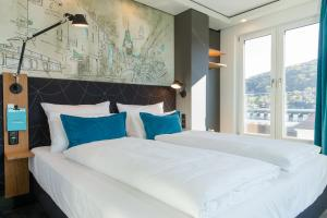 A bed or beds in a room at Motel One Freiburg