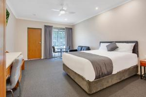 A bed or beds in a room at Manifold Motor Inn