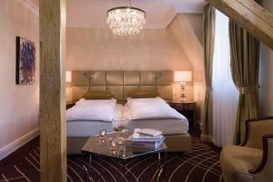 A bed or beds in a room at Waldhaus Flims Wellness Resort, Autograph Collection