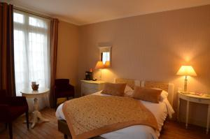 A bed or beds in a room at Villa Augeval Hôtel de charme & Spa
