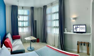 A television and/or entertainment center at Holiday Inn Express Ciudad de las Ciencias, an IHG Hotel