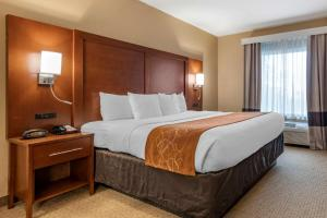 A bed or beds in a room at Comfort Suites Orlando Airport