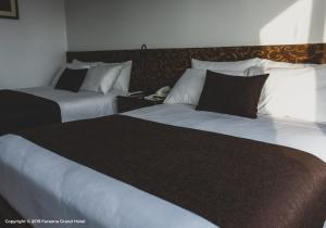 A bed or beds in a room at Faraona Grand Hotel