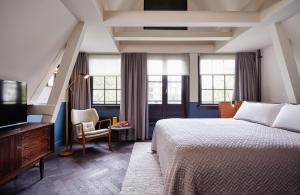 A bed or beds in a room at The Hoxton, Amsterdam