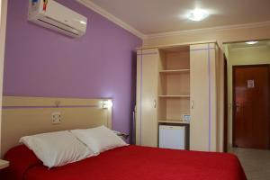 A bed or beds in a room at Bombinhas Praia Apart Hotel - unidade rua Bem Te Vi
