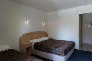 A bed or beds in a room at Nunawading Motor Inn