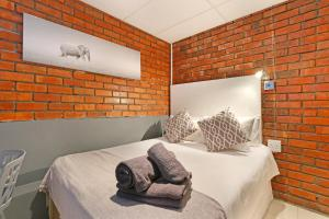 A bed or beds in a room at Happy Rhino Hotel