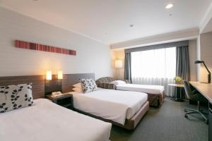 Кровать или кровати в номере Nagoya Tokyu Hotel