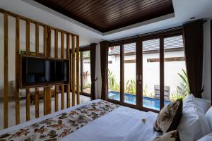 A bed or beds in a room at The Calna Villa Bali