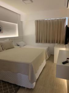 A bed or beds in a room at Beach Place Cumbuco Apto 04