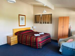 A bed or beds in a room at Blenheim Road Motor Lodge