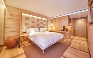 A bed or beds in a room at Falkensteiner Hotel Kronplatz - Adults only