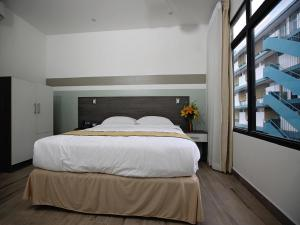 A bed or beds in a room at Hotel Cultura Plaza