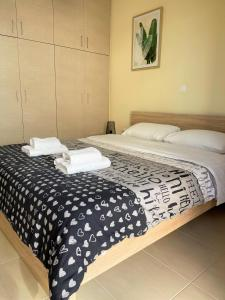A bed or beds in a room at Boho Apartment near Athens Airport