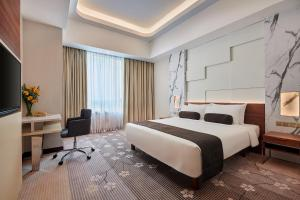 A bed or beds in a room at The Boulevard – A St Giles Hotel, Kuala Lumpur