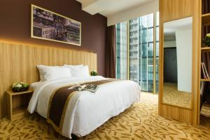 A bed or beds in a room at Bay Hotel Ho Chi Minh
