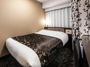 A bed or beds in a room at APA Hotel SHIN-OSAKA MINAMIKATA EKIMAE