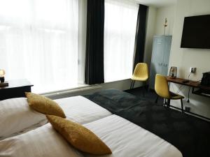 Een bed of bedden in een kamer bij Hotel Café Restaurant De Posthoorn