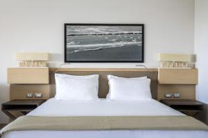 A bed or beds in a room at Capovaticano Resort Thalasso Spa