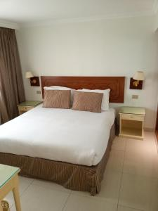 A bed or beds in a room at Cairo Pyramids Hotel