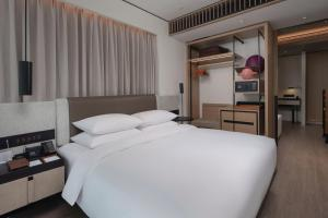 A bed or beds in a room at Hotel Kapok Shenzhen Luohu