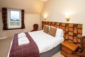 A bed or beds in a room at The Inn @ Aird a' Bhasair