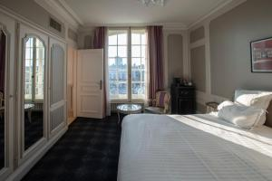 A bed or beds in a room at Grand Hotel De La Reine - Place Stanislas