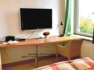 A television and/or entertainment centre at Ferienhaus Us lütt Hus und das Zimmer Linde im Haupthaus