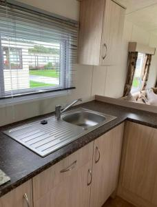 A kitchen or kitchenette at Home from Home Caravan Hire Havens Thorpe Park Cleethorpes