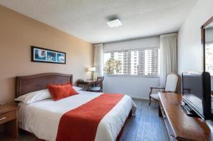 A bed or beds in a room at Palladium Business Hotel
