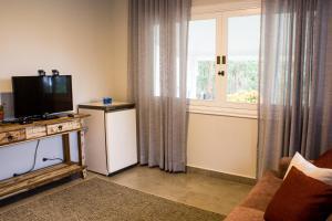 Uma TV ou centro de entretenimento em Recanto Da Paz Hotel Fazenda