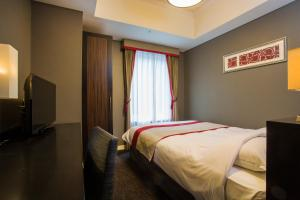 A bed or beds in a room at Hotel Monterey Akasaka