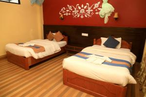 A bed or beds in a room at Chitwan Forest Resort , Chitwan National Park