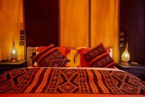 Een bed of bedden in een kamer bij Merzouga Paradise Luxury Camp