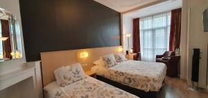 A bed or beds in a room at Hotel Bor Scheveningen