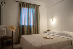A bed or beds in a room at Aphrodite Hotel & Apartments