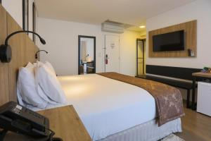 A bed or beds in a room at Nobile Suites Maringa