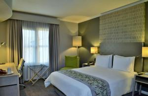 A bed or beds in a room at Holiday Inn Johannesburg Airport, an IHG Hotel