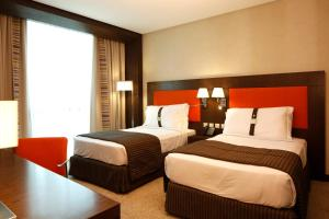 A bed or beds in a room at Holiday Inn Meydan, an IHG Hotel