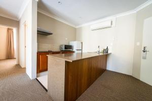 A kitchen or kitchenette at The Belmore All-Suite Hotel