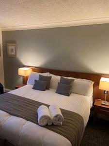 A bed or beds in a room at Caledonian Hotel